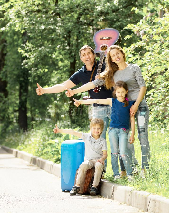 Fun family friendly stops a passing car. Cheerful friendly family with suitcases stops passing car royalty free stock images