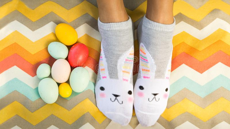 Fun Flat Lay of person wearing bunny socks with Easter eggs. blanket. Copy space. Fun bright and colorful Flat Lay of person wearing bunny socks with Easter eggs royalty free stock image