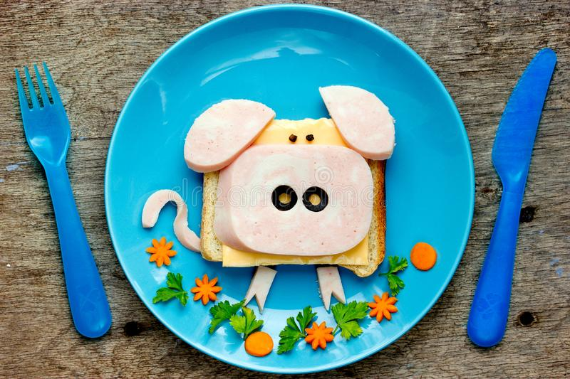 Fun food art idea for kids breakfast - funny pig sandwich. With cheese, ham and olives on blue plate top view stock photography