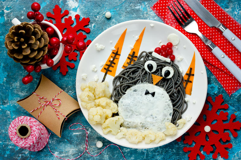Fun food art idea for kids - penguin black spagehetti with fried royalty free stock photo