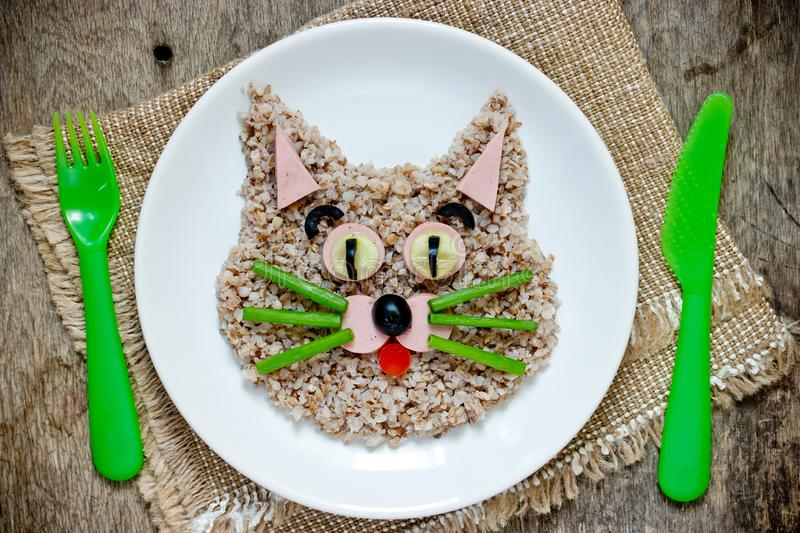 Fun food for children - healthy buckwheat porridge shaped cat face. On white plate top view royalty free stock photos
