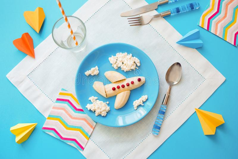 Fun food idea for kids. children`s Breakfast: plane made of banana and clouds made of curd on a blue plate stock image