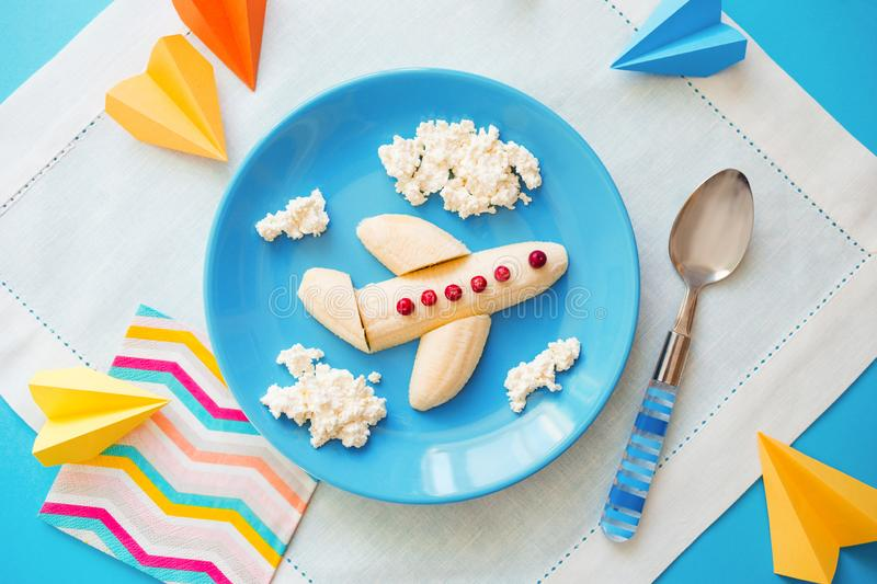 Fun food idea for kids. children`s Breakfast: plane made of banana and clouds made of curd on a blue plate stock photos