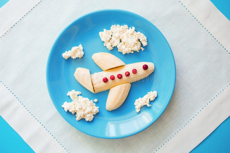 Fun food idea for kids. children`s Breakfast: plane made of banana and clouds made of curd on a blue plate stock photo