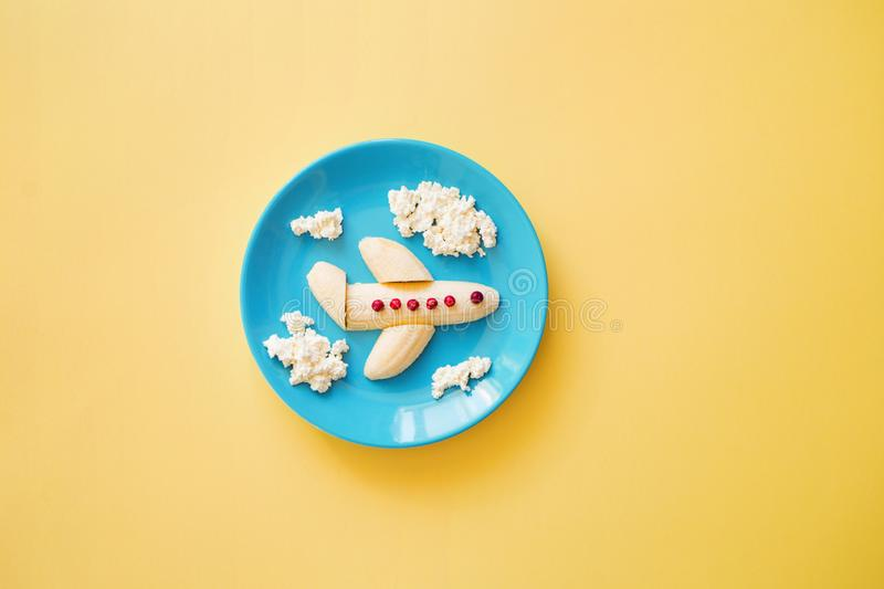 Fun food idea for kids. children`s Breakfast: plane made of banana and clouds made of curd on a blue plate royalty free stock photography