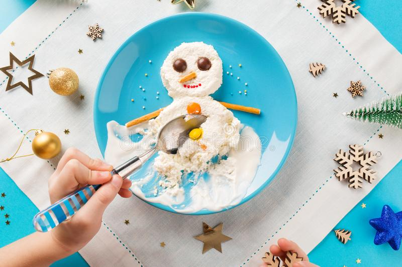 Fun food idea for kids. Christmas children`s Breakfast: snowman of cottage cheese on a blue plate. royalty free stock image