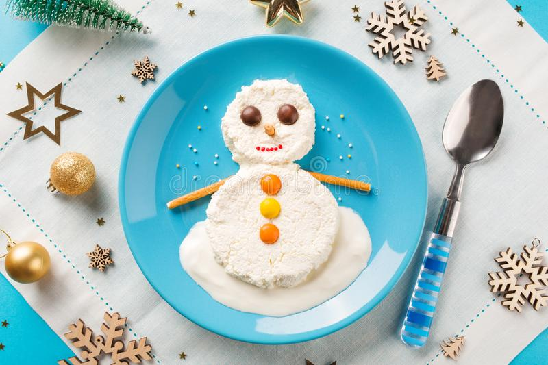 Fun food idea for kids. Christmas children`s Breakfast: snowman of cottage cheese on a blue plate. Fun food idea for kids. Christmas children`s Breakfast royalty free stock photos