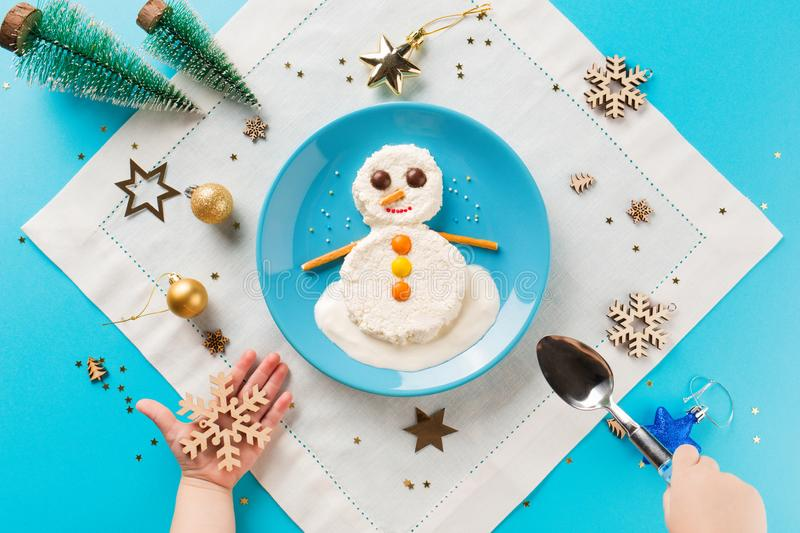 Fun food idea for kids. Christmas children`s Breakfast: snowman of cottage cheese on a blue plate. royalty free stock images