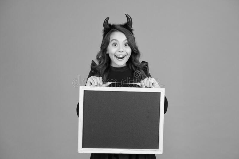 Fun and fun again. happy halloween. autumn holiday sales. copy space. small girl school blackboard. little imp red horns royalty free stock photography