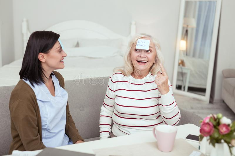 Happy elder woman and caregiver playing game. Always fun. Gay elder women and caregiver laughing while playing game stock photos
