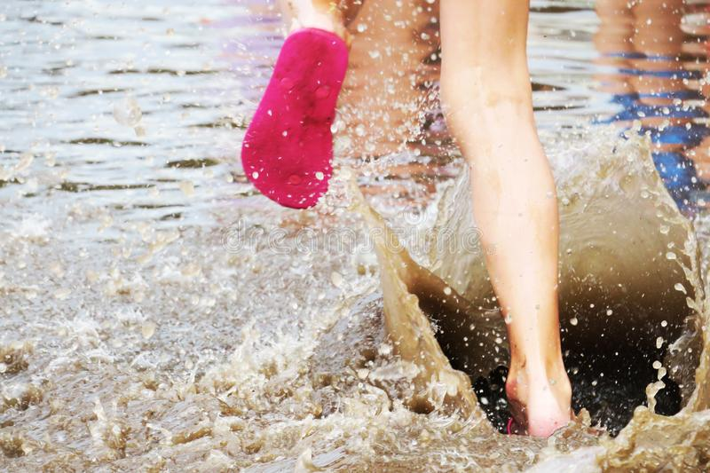 Jumping with slippers in the puddle royalty free stock photo