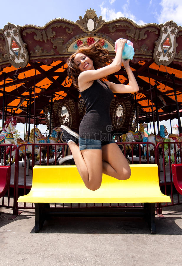 Fun girl jumping at Carousel stock photo
