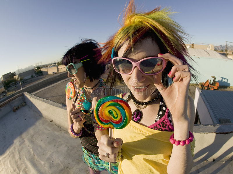 Fun girls on the roof with lollipops. Fisheye shot of girls in brightly colored clothing on a roof with sunglasses and lollipops stock images