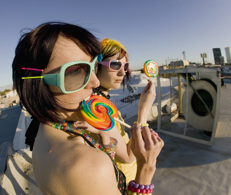 Fun girls on the roof with lollipops. Fisheye shot of girls in brightly colored clothing on a roof with sunglasses and lollipops royalty free stock photos