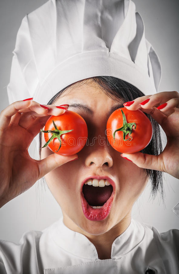 Fun goofy chef with tomato eyes. Fun goofy young female Asian chef in her white toque and uniform holding two juicy ripe red tomato over her eyes while laughing stock photo