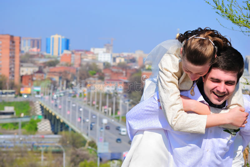 Fun groom and bride. The groom and the bride laugh against a city royalty free stock images