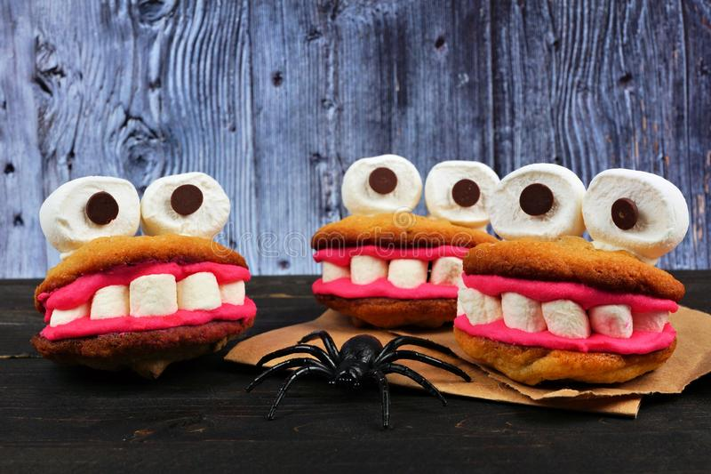 Halloween monster cookies against an old wood background. Fun Halloween monster cookie treats. Side view against a spooky old wood background stock photos