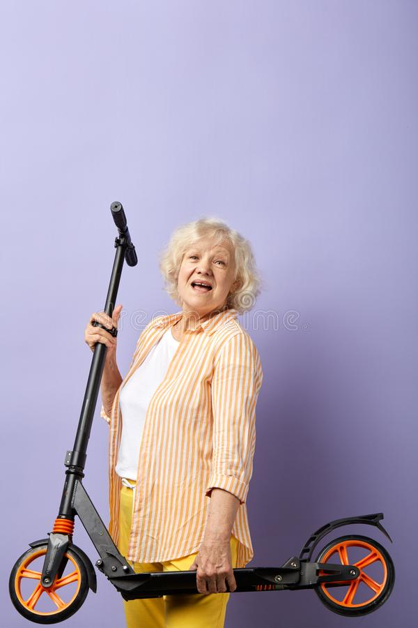 So fun. Happy elderly woman keeps in hands scooter ready for a ride. royalty free stock photo