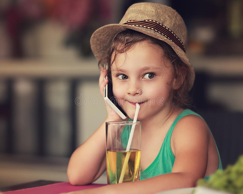 Fun happy kid girl talking on mobile phone and drinking apple juice in cafe. Toned closeup portrait stock images