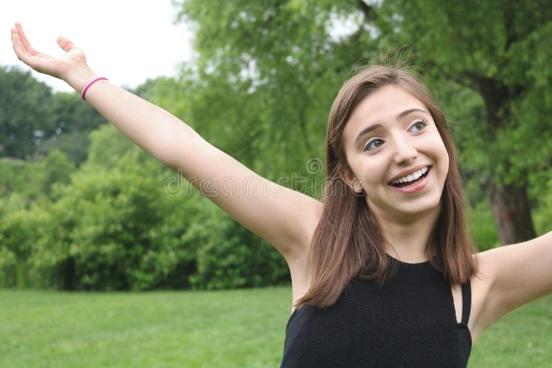Fun happy young girl at a lush green park arms up having fun looking away stock images