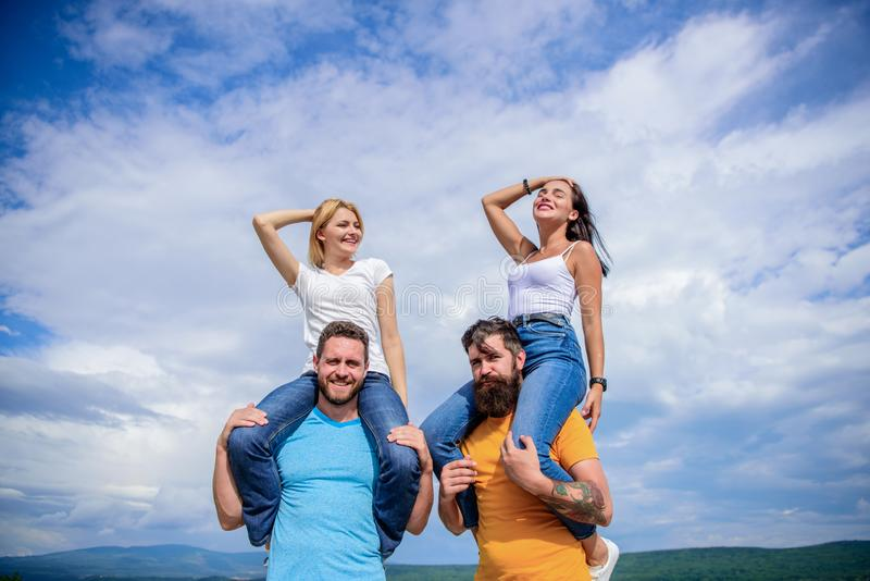 The fun has just begun. Playful couples in love smiling on cloudy sky. Happy men piggybacking their girlfriends. Loving royalty free stock image