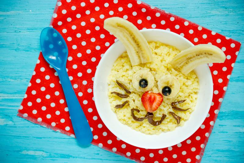 Fun and healthy breakfast idea for kids - Easter bunny millet porridge with milk royalty free stock images