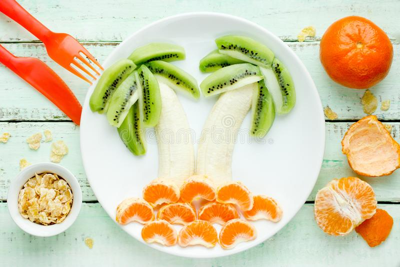 Fun and healthy fruit salad for kids, kiwi banana mandarin palms royalty free stock photo