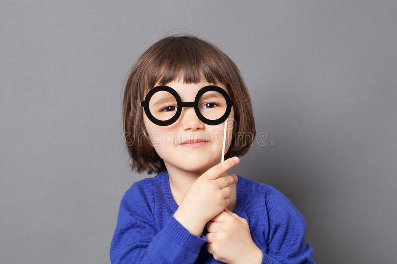Fun kid glasses concept for wise preschool child. Fun kid glasses concept - wise preschool child holding fake black round eyeglasses for playing like adult or royalty free stock image