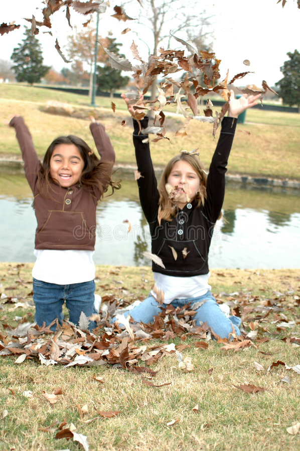 Fun in the Leaf's. Beautiful sisters sitting on the ground in fall leaves. Blur action of two sister throwing leaf's in the air stock images