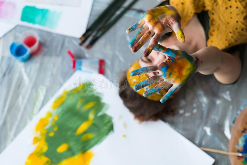 Fun leisure artist floor hands colorful paint. Fun leisure. Top view of creative female artist lying down on floor showing hands dirty with colorful paint. Blur stock image