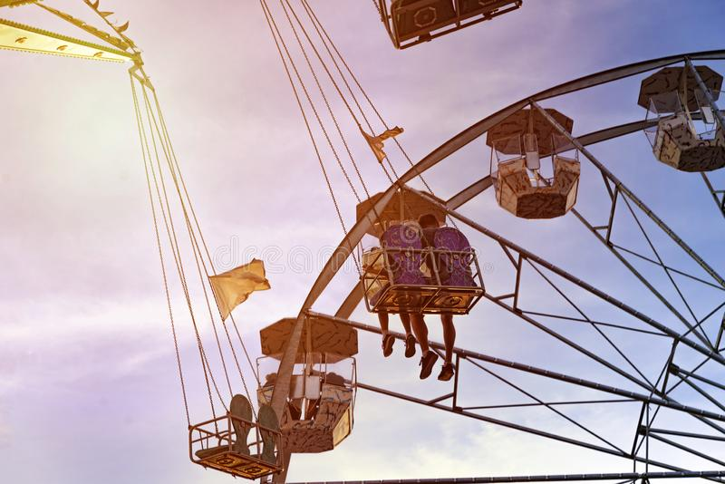 Fun in the lunapark, people on the rollercoaster and big wheel, sunset stock image
