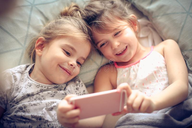 Fun with mobile phone. Two little girl using smart phone together royalty free stock photography