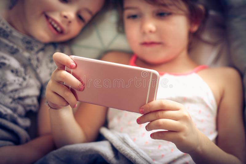Fun with mobile phone. Two little girl using smart phone together royalty free stock image