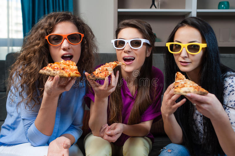 Fun Movie night with Girlfriends. Three girls eating popcorn while watching a movie on tv at home stock photos