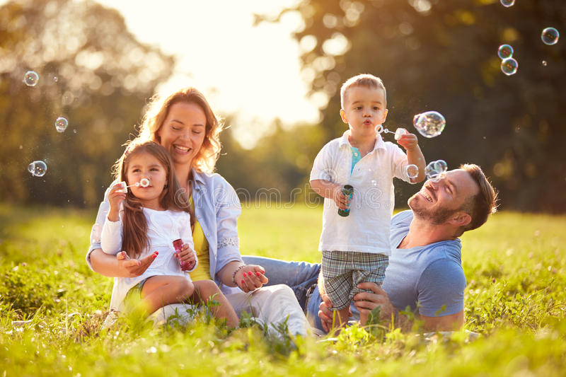 Fun in nature with soap bubbles. Parents with children having fun in nature with soap bubbles stock photography