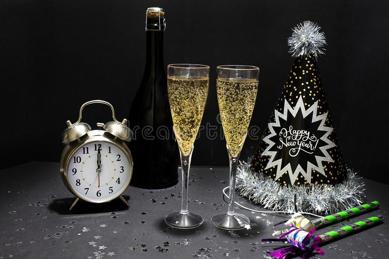 Fun New Year's Eve Holiday Champagne With Hats, Glitter, Confetti, Clock & Noisemakers. New Year's Eve champagne with party hats, glitter, confetti royalty free stock image