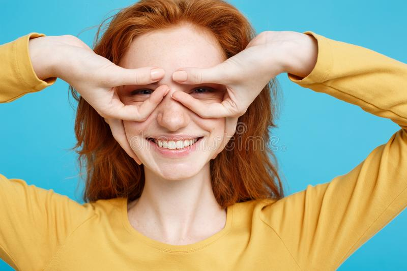 Fun and People Concept - Headshot Portrait of happy ginger red hair girl with freckles smiling and making finger glasses stock images