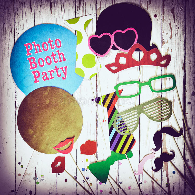 Fun photo booth party background. With colorful paper fashion accessories, lips, moustaches and balloons with text - Photo Booth Party - surrounded by a royalty free stock images