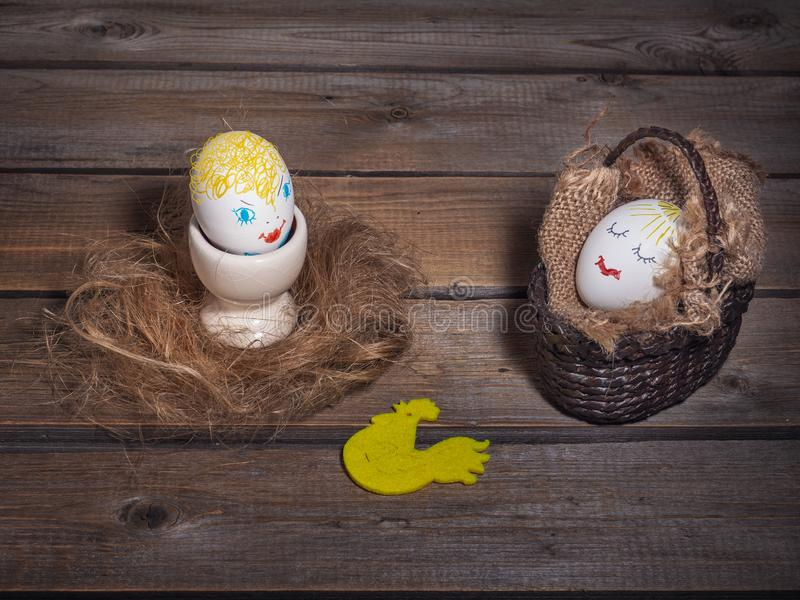 Fun picture with eggs with painted faces. One is in a wicker basket, and the other is on an egg holder royalty free stock photography