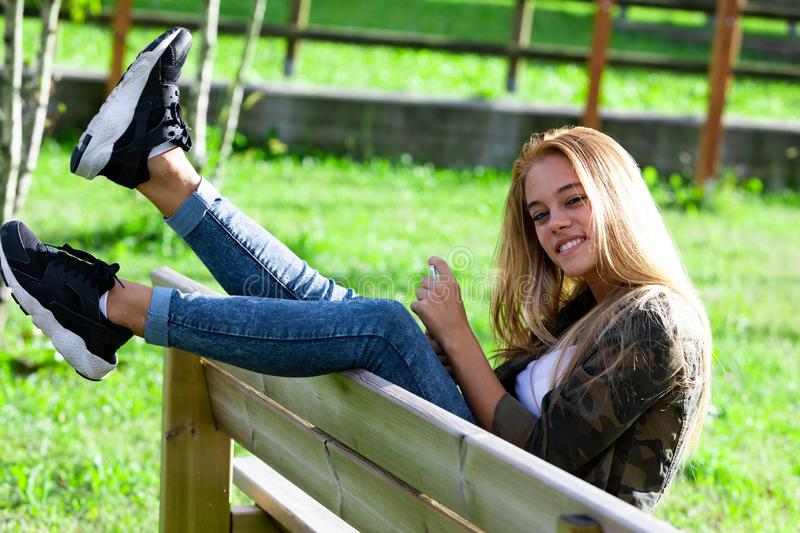 Fun playful young woman sitting on a bench. Fun playful young woman sitting on a park bench swinging her feet in the air over the back grinning at the camera stock photos