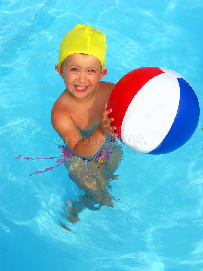 Fun in the pool. A pretty little girl playing in pool with a beach ball stock image
