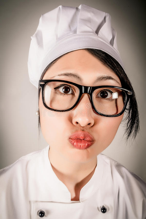 Fun portrait of chef making a kissing gesture. Fun portrait of a young female Asian chef wearing glasses and a toque making a kissing gesture puckering up her stock image