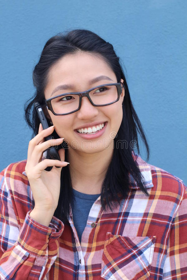 Fun portrait of a laughing attractive young Asian woman wearing glasses chatting on a mobile phone laughing at the camera royalty free stock photo