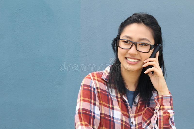 ba7290dcfd32 Fun portrait of a laughing attractive young Asian woman wearing glasses  chatting on a mobile phone