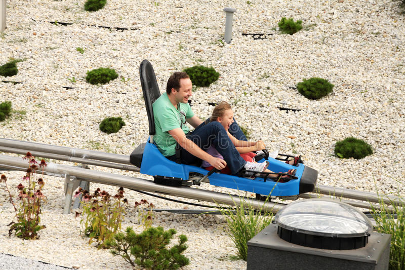 Fun on the roller coaster. Father and daughter are riding a roller coaster fast stock image