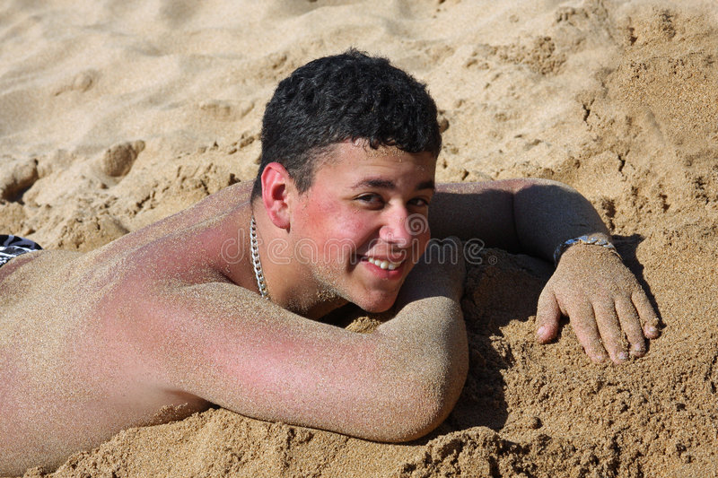 Fun in the Sand. A teenage boy covered with sand having fun on the beach stock photos