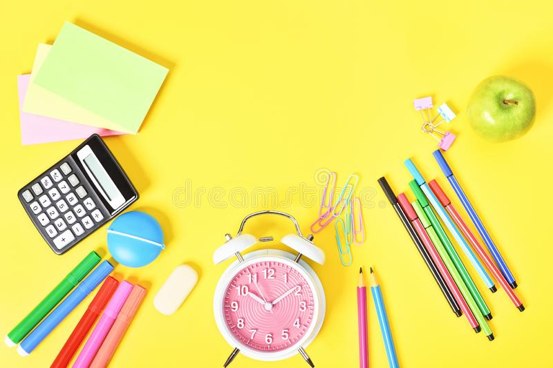 Fun scattered back to school stationary. Fun school statuonary scattered at the bottom on yellow background royalty free stock image