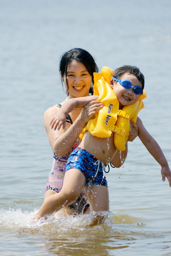 Fun at sea. Picture of a little chinese boy playing with sea water and having great fun with his mother royalty free stock image