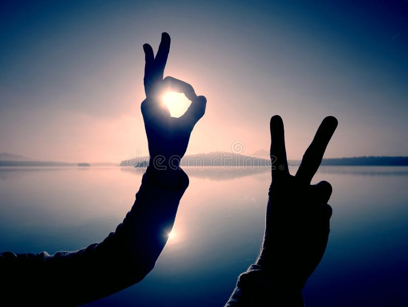 Fun shadow play. Shadow of hand symbol. Fingers gesturing. Frame on rising Sun, wrist, white, water, victory, touch, symbolic, summer, sky, silhouette, shot royalty free stock images