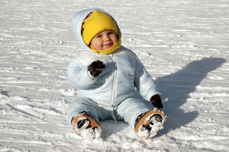 Fun in the snow. A little and smiling baby boy playing in the snow royalty free stock photos